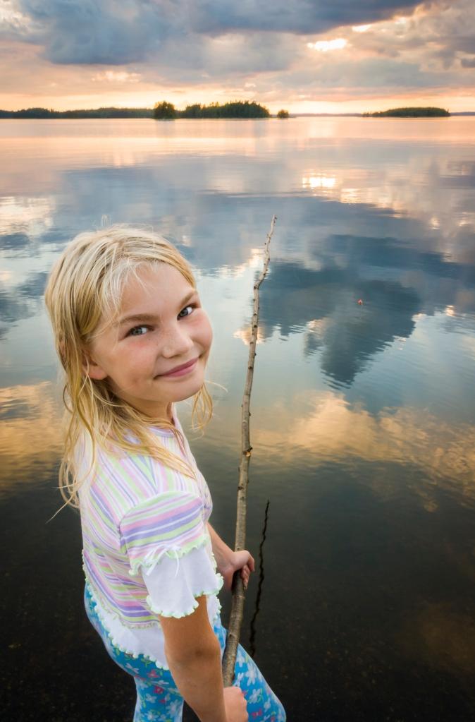 Tyttö onkimassa järvellä.